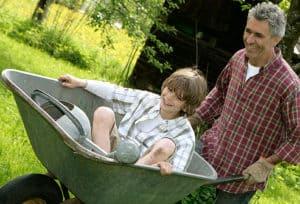father_pushing_son_in_wheelbarrow